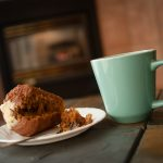 Indulge in a hot coffee and breakfast muffin in front of a cozy fireplace